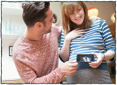 Happy couple holding a picture of a sonogram of their baby