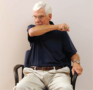 Man illustrating coughing into your elbow while sitting
