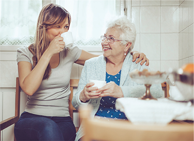An older and middle aged woman sitting together enjoying a cup of coffee
