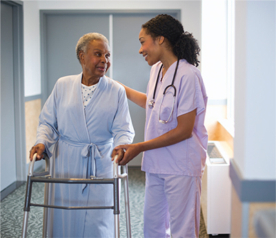 A nurse assisting a patient as she walks down a hallway with a walker