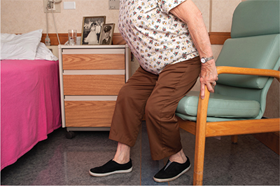 Woman illustrating properly sitting on or standing from a chair after spine surgery