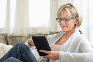 older woman using a tablet while lounging on couch