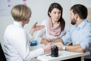couple conversing with doctor