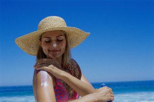 woman on a beach in a sunhat applying sunscreen to her arm